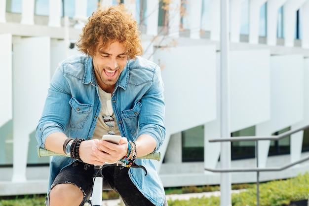 通りで携帯電話を使っているときに微笑むハンサムな若い男のポートレート。