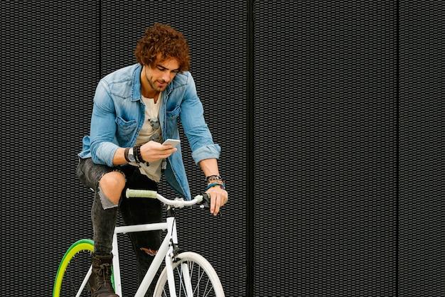彼が通りで彼の携帯電話を使用しているときに笑っているハンサムな若い男の肖像画。