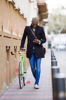거리에서 휴대전화와 고정 기어 자전거를 사용하는 잘생긴 청년의 초상화.