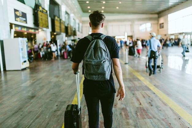 空港を歩いているハンサムな若い男の肖像画。