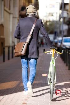 거리에서 자신의 자전거와 함께 걷는 잘생긴 젊은 남자의 초상화.