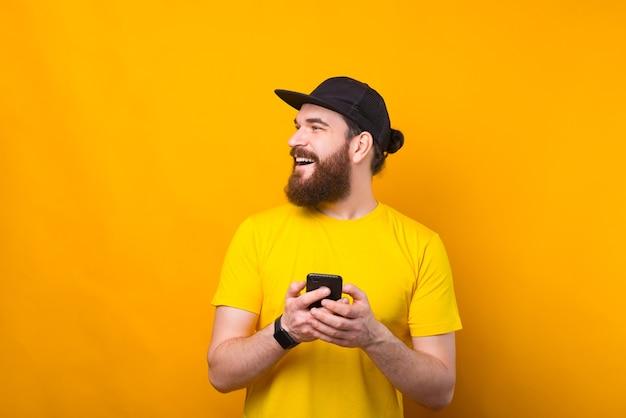 スマートフォンを保持し、コピースペースで横を見てひげを持つハンサムな若い男の肖像画