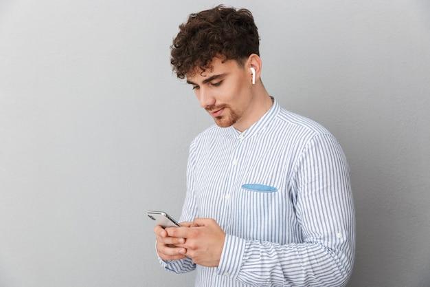 灰色の壁に隔離された携帯電話を保持し、入力するイヤポッドを持つハンサムな若い男の肖像画