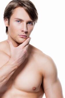 흰 벽에 얼굴 가까이 손으로 잘 생긴 젊은 남자의 초상화.