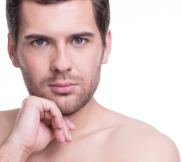 Портрет красивого молодого человека с рукой возле лица на белой стене.