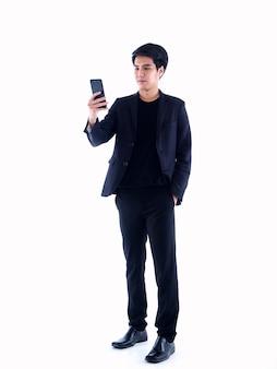 白の上に立っている間ビデオ通話を持っているスマートフォンを持つハンサムな若い男の肖像画