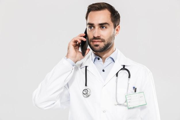 Портрет красивого молодого врача со стетоскопом, работающего в клинике и говорящего по мобильному телефону, изолированного над белой стеной