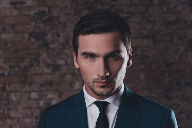 黒のスーツを着ているハンサムな若い金持ちの男の肖像画