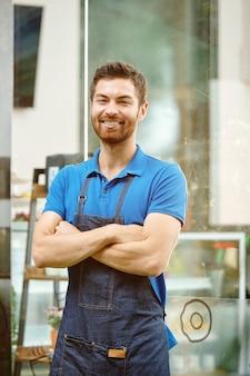 Портрет красивого молодого владельца магазина в джинсовом фартуке, стоящего у окна продовольственного магазина