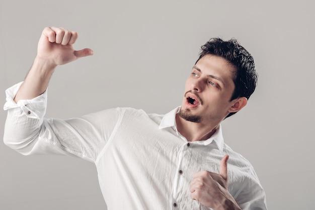 Портрет красивого молодого улыбающегося брюнет человека в белой рубашке, показывая большие пальцы руки вверх жест на сером фоне. мягкий свет