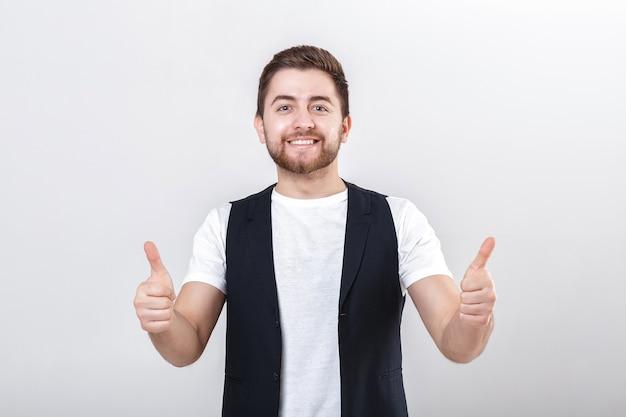 Портрет красивого молодого улыбающегося брюнет человека в белой рубашке, показывая большие пальцы руки вверх жест на сером фоне.