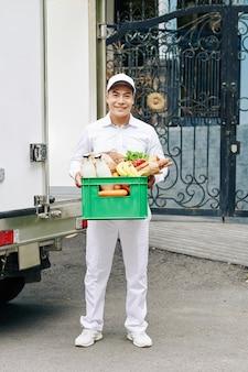 우유 병, 신선한 빵과 과일 플라스틱 상자를 들고 잘 생긴 젊은 베트남 택배의 초상화
