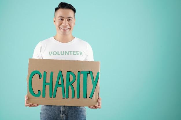 Портрет молодого красивого добровольца, показывающего большой плакат с благотворительной надписью