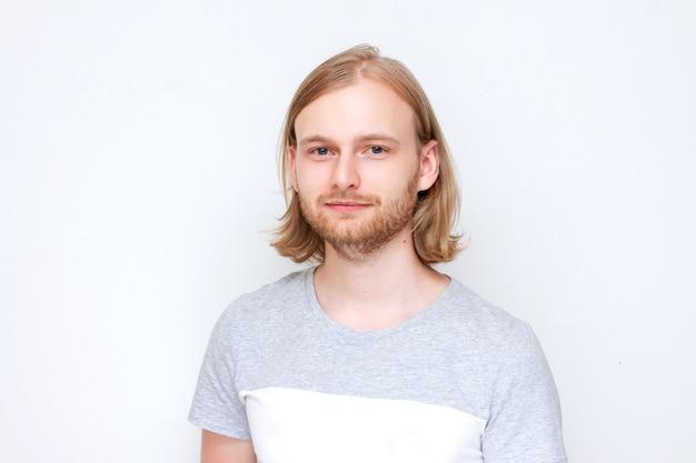 Портрет красивого молодого молодого парня с длинными светлыми волосами в футболке, на сером фоне.
