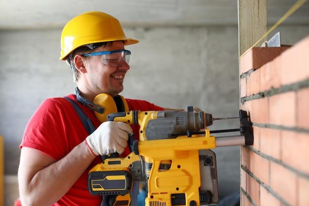 建設された壁に穴をあけるために穴あけ機を使用する便利屋ビルダーの肖像画。修理または修正、産業労働者、ジョブ完了のための器具
