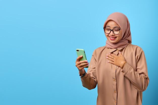 胸に別の手で携帯電話を使用して幸せの若いアジアの女性の肖像画