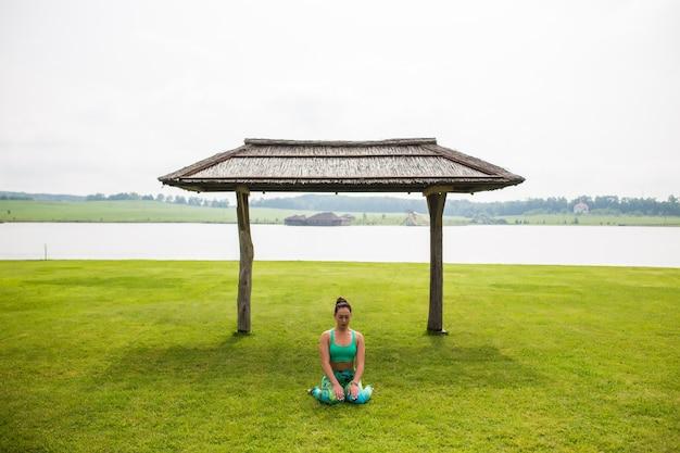Портрет счастья молодой женщины, практикующей йогу на открытом воздухе
