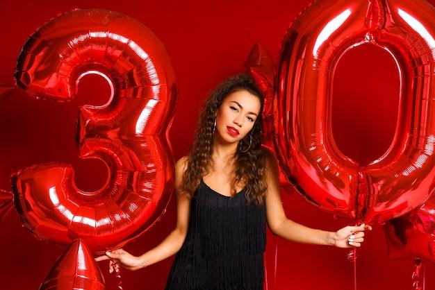赤い風船と赤い壁に幸せな30歳の女性の肖像画