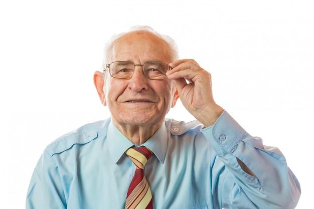 Портрет счастливого 90-ти летнего старшего человека держа стекла, усмехаясь и смотря камеру изолированную на белой предпосылке.