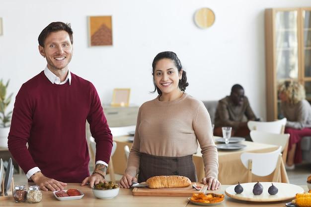 幸せな大人のカップルの肖像画と屋内でのディナーパーティーのために料理しながら笑顔、