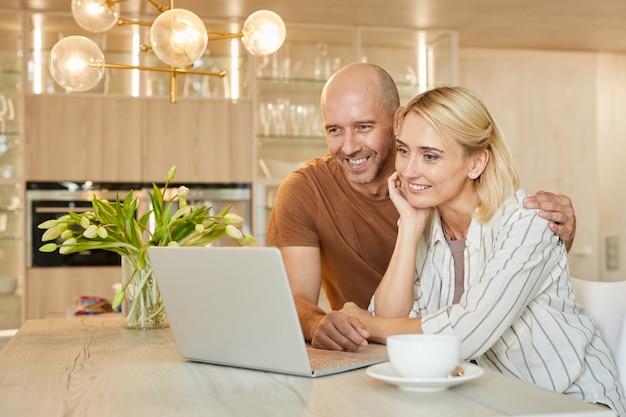 Портрет счастливой взрослой пары, смотрящей на экран ноутбука и улыбающейся во время разговора по видеочату с семьей