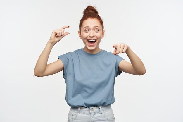 머리를 가진 행복, 성인 빨간 머리 여자의 초상화는 롤빵에 모여. 파란색 티셔츠와 청바지를 입고. 약간의 크기와 웃음을 보여줍니다. 보고 하 고 흰 벽 위에 절연 가리키는