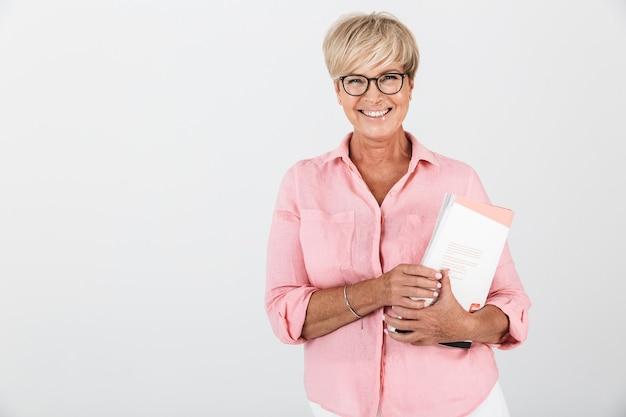 Портрет счастливой взрослой женщины в очках, держащей учебную книгу, изолированную над белой стеной в студии