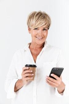 スタジオで白い壁の上に分離された携帯電話と持ち帰りのコーヒーカップを保持している短いブロンドの髪を持つ幸せな大人の女性の肖像画