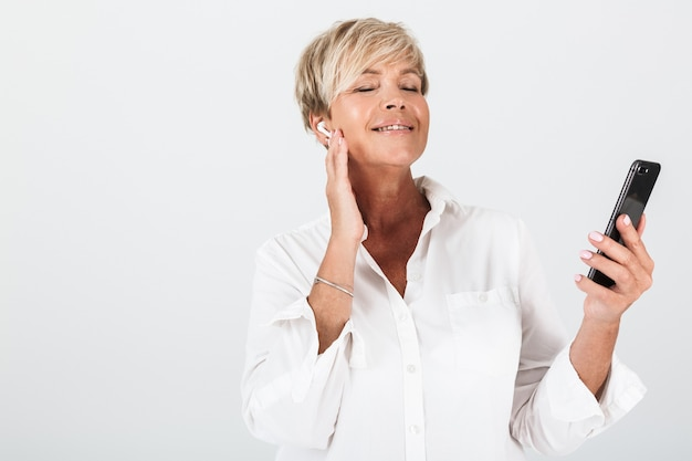 スタジオで白い壁の上に分離されたイヤポッドと携帯電話を使用して短いブロンドの髪を持つ幸せな大人の女性の肖像画