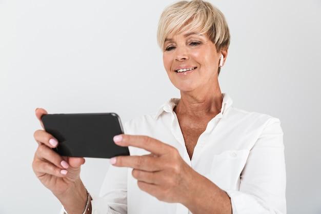 イヤポッドを身に着けて、スタジオで白い壁に隔離された携帯電話を保持している短いブロンドの髪を持つ幸せな大人の女性の肖像画