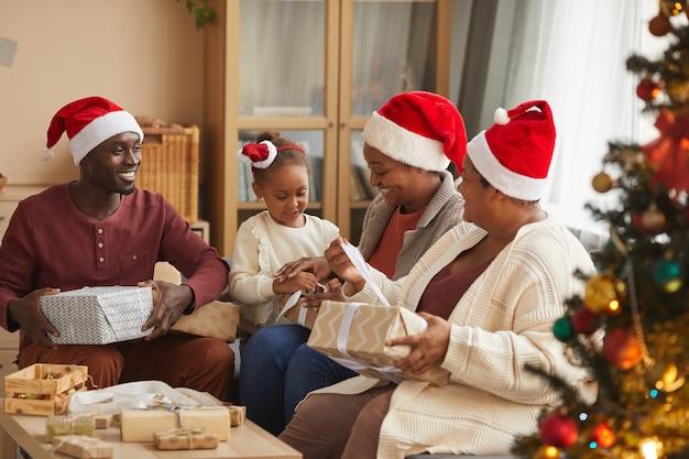 산타 모자를 쓰고 집에서 휴가 시즌을 즐기는 동안 크리스마스 선물을 여는 행복 한 아프리카 계 미국인 가족의 초상화