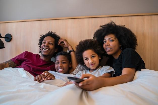 自宅の寝室のベッドで映画を見て幸せなアフリカ系アメリカ人の家族の肖像画。ライフスタイルと家族の概念。