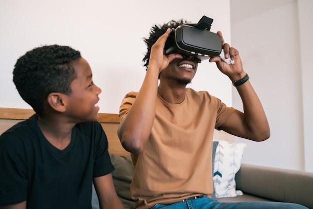 행복 한 아프리카 계 미국인 아버지와 아들의 초상화 소파에 앉아 집에서 vr 안경으로 비디오 게임을 함께