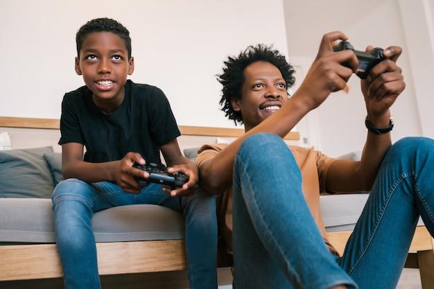 幸せなアフリカ系アメリカ人の父と息子のソファーソファに座って、家で一緒にコンソールビデオゲームをプレイの肖像画。家族と技術の概念。