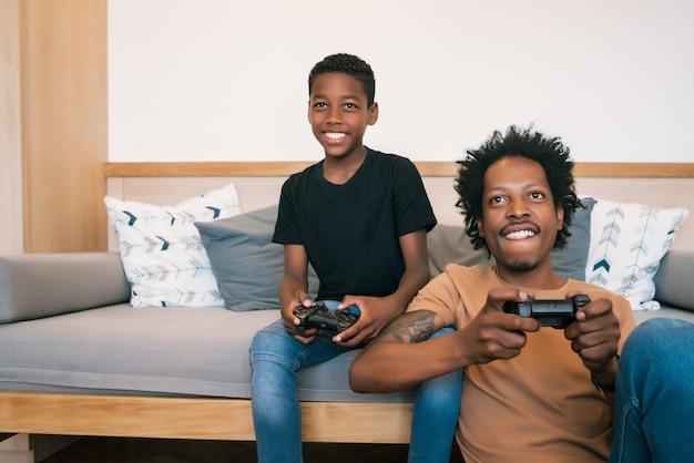 행복 한 아프리카 계 미국인 아버지와 아들 소파 소파에 앉아 집에서 콘솔 비디오 게임을 함께하는 초상화. 가족 및 기술 개념.