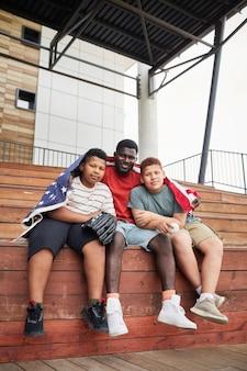 Портрет счастливого афроамериканского отца, обнимающего сыновей-подростков, покрытых американским флагом, пока они сидят на скамейке для отбеливания
