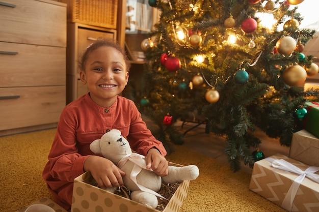 Портрет счастливой афро-американской девушки, открывающей рождественские подарки, сидя у дерева дома и улыбаясь в камеру, скопируйте пространство