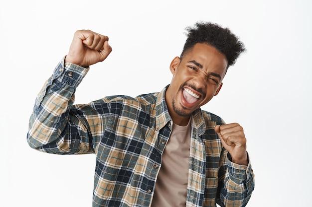 Портрет счастливого афро-американского парня, который поет, поднимает кулак и кричит от радости, взволнованный победой, празднует победу, выигрывает игру, стоит в клетчатой рубашке на белом