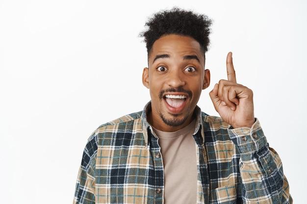 Портрет счастливого афро-американского парня, говорящего отличные новости, поднимающего палец вверх и улыбающегося, взволнованного смеха, имеющего отличную идею, предлагающего план на белом