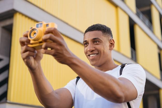 Портрет счастливого афро-американского фотографа, снимающего на улице вдохновение путешествия
