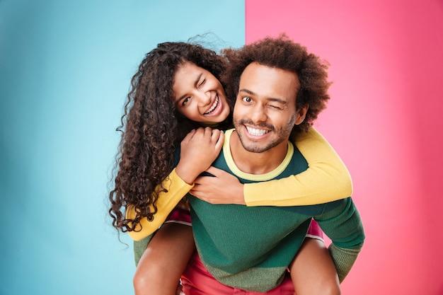 楽しんでウインクする幸せなアフリカ系アメリカ人の若いカップルの肖像画