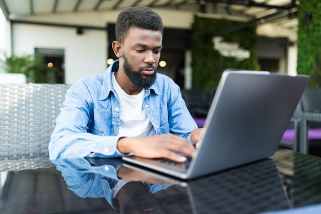 レストランでラップトップで作業しながら電話を使用して幸せなアフリカの実業家の肖像画