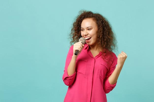 カジュアルな服を着て踊る幸せなアフリカの女の子の肖像画、スタジオの青いターコイズブルーの壁の背景に分離されたマイクで歌を歌います。人々の誠実な感情、ライフスタイルのコンセプト。コピースペースをモックアップします。