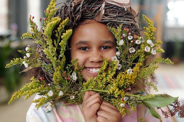 꽃 화환과 함께 포즈를 취하는 카메라에 웃는 행복한 아프리카 소녀의 초상화