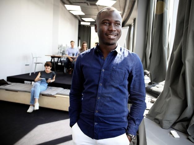작업 환경에서 카메라를보고 행복 한 아프리카 남자의 초상화.