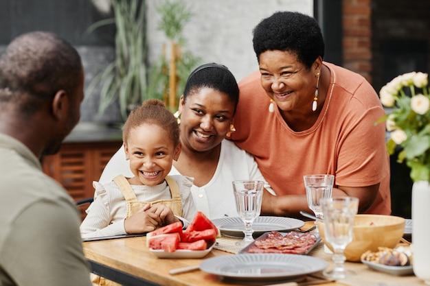 テラスのコピースペースで屋外で一緒に夕食を楽しんで幸せなアフリカ系アメリカ人家族の肖像画
