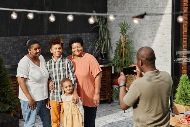 テラス屋外コピースペースで写真のポーズをとって幸せなアフリカ系アメリカ人家族の肖像画