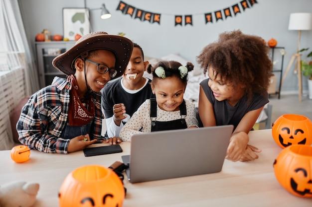 自宅でラップトップを使用している間、ハロウィーンの衣装を着て幸せなアフリカ系アメリカ人の子供たちの肖像画とビデオ...