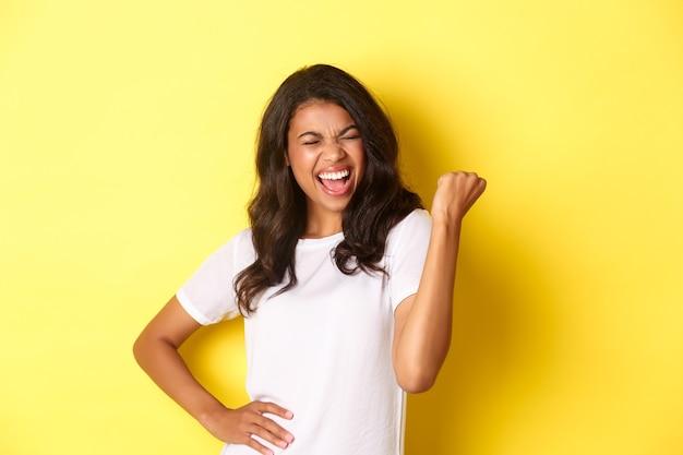 幸せなアフリカ系アメリカ人の女性の肖像画の勝利と勝利の拳ポンプと叫びを作る