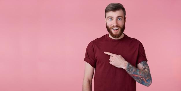 Портрет счастливого изумленного молодого красивого рыжего бородатого мужчины в красной рубашке, хочет привлечь ваше внимание слева на копировальном пространстве, указывая пальцами и смотрит на него, стоит на розовом фоне.
